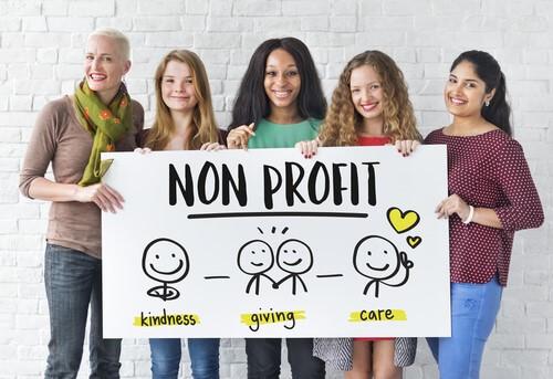 """5 נשים מחייכות עם שלט """"ללא מטרות רווח"""""""